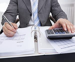 Accountant sitting at desk using a calculator